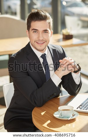 A little break. Vertical shot of a young handsome businessman smiling to the camera resting at the local cafe - stock photo