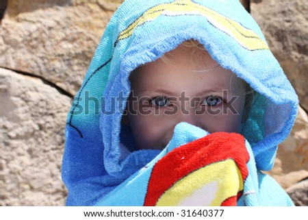 a little caucasian child totally covered with a towel after swimming to protect against the damage of the sun