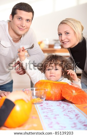 a little child  eating a pumpkin and his parents - stock photo