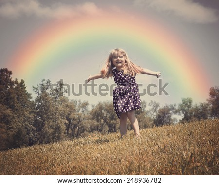 A little child is dancing in an open grass field with wind blowing in her hair and a rainbow in the background for a freedom or spring concept. - stock photo