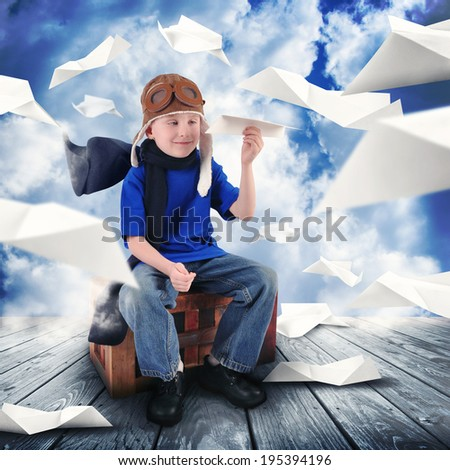 A little child is holding a paper airplane in the sky dreaming about being a pilot flying. The boy is happy for a career or dream concept. - stock photo
