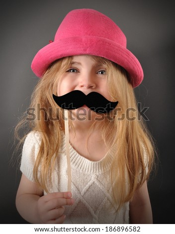 A little child is holding a pretend mustache disguise for a humor or fun concept. The girl is smiling and happy with a pink hat. - stock photo