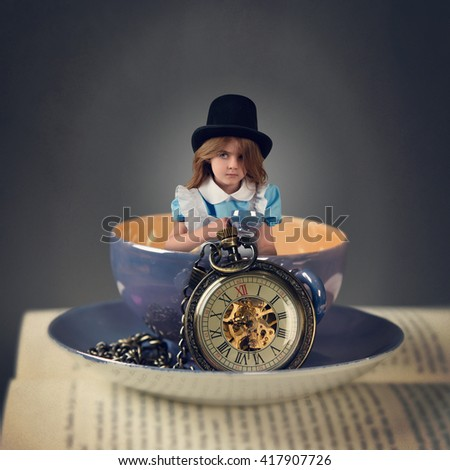 A little child is sitting in a big tea cup on a book with a time clock for a magical story or fairy tale concept. - stock photo