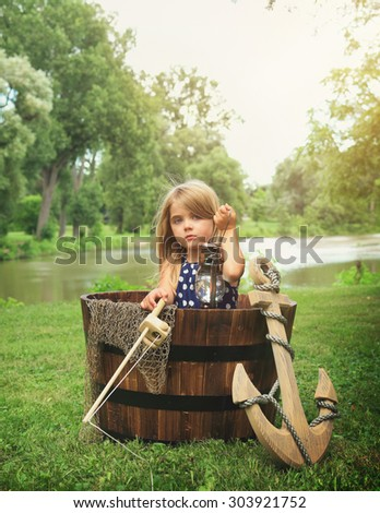 A little child is sitting in a wooden boat with an anchor by the water pretending to fish for an imagination or exploration concept. - stock photo