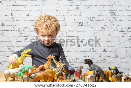 a little child plays with toys animals and dinosaur - stock photo