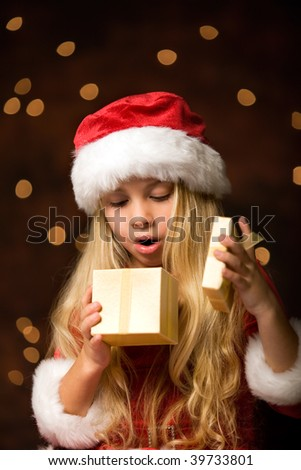 a little christmas girl opens a christmas gift and is surprised - stock photo