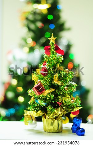 A little Christmas tree with defocused Christmas tree background - stock photo