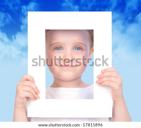 A little cut boy is holding a white frame and his face is looking through it. There are clouds in the background and he has blue eyes. Use it for a future or imagination concept. - stock photo