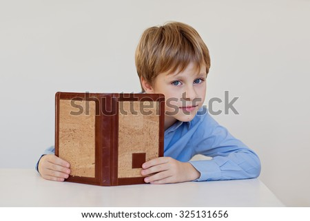 A little cute boy in a blue shirt reading a book sitting at the table. - stock photo