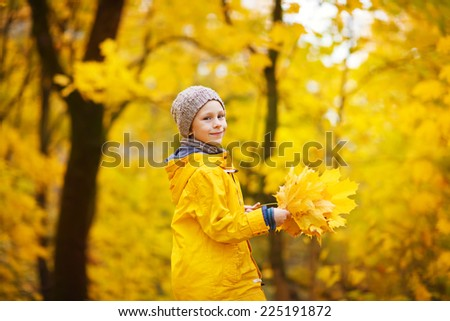 A little cute boy in a bright yellow jacket and grey knitted hat walking in a park on a sunny autumn day - stock photo