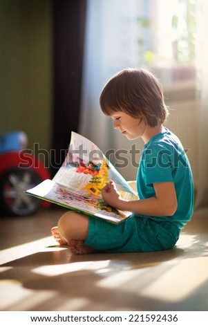 A little cute boy reading a book sitting on the floor - stock photo
