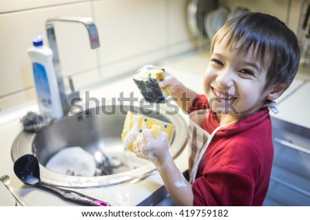 A little cute boy washing dishes - stock photo