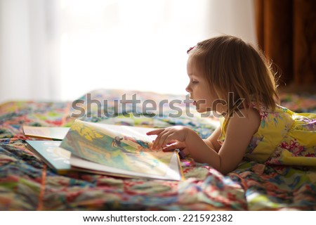 A little cute girl in a yellow dress reading a book lying on the bed - stock photo
