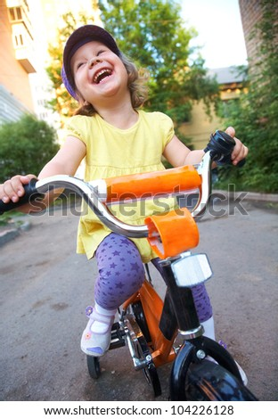 A little cute girl rides a bicycle down the street