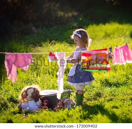 A little cute girl washing her dolls and toys and doing the laundry in a small aluminium basin behind the clothesline in the meadow on a sunny summer day - stock photo