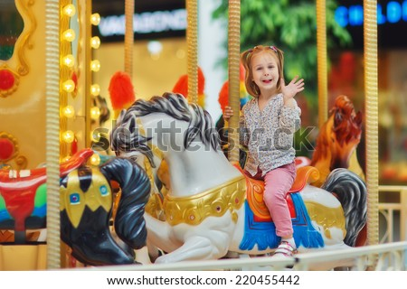 A little cute smiling girl having a ride on the merry-go-round  - stock photo