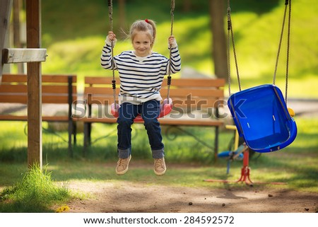 A little cute smiling girl in a striped pullover playing on a children's playground on a sunny spring day  - stock photo