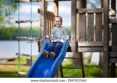 A little cute smiling girl in a striped pullover playing on a children's playground on the river bank on a sunny spring day  - stock photo