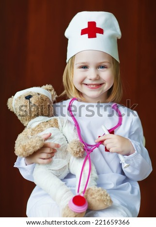 A little cute smiling girl in a white coat playing a doctor with a teddy bear close up - stock photo