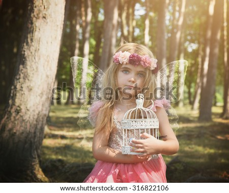 A little fairy angel girl has sparkle wings with a birdcage in the enchanted woods for a fantasy or magical concept. - stock photo
