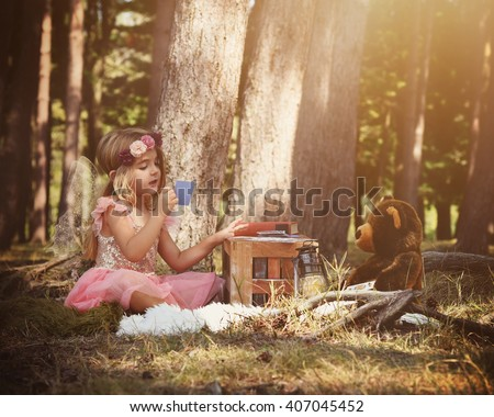 A little fairy girl is sitting in the woods playing a card game with a teddy bear for an imagination or fairy tale concept.  - stock photo
