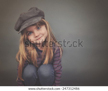 A little fashion girl with long hair and blue eyes wearing a hat is smiling with copyspace on a gray background for a happiness or style concept. - stock photo