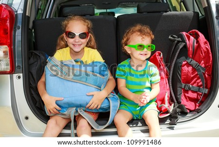 a little girl  and boy sitting in the car with backpacks - stock photo