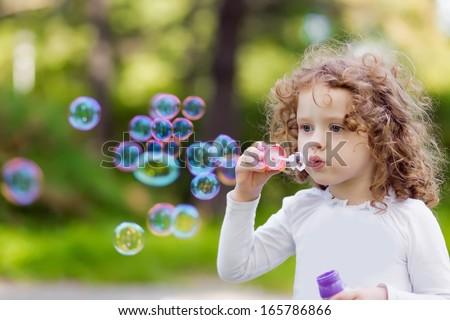 A little girl blowing soap bubbles, closeup portrait beautiful curly bab - stock photo