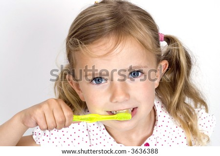 A little girl brushing her teeth with a brightly colored toothbrush - stock photo