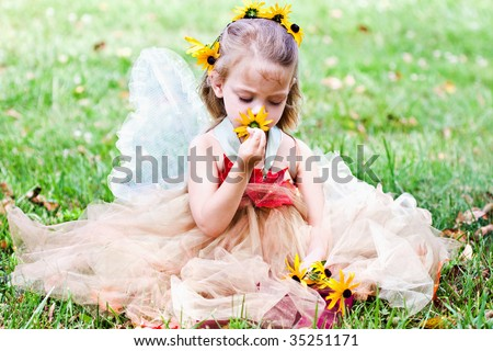 A little girl dressed as a woodland fairy for Halloween gathering flowers.  - stock photo