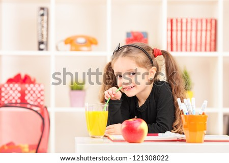 A little girl drinking a juice at home - stock photo