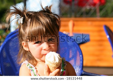 A little girl eating ice-cream - stock photo