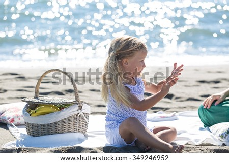 a little girl enjoying a picnic on the beach