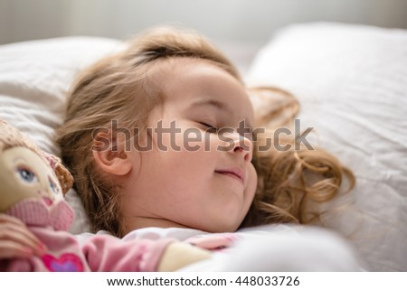 a little girl falls asleep in bed with soft doll, white bed - stock photo