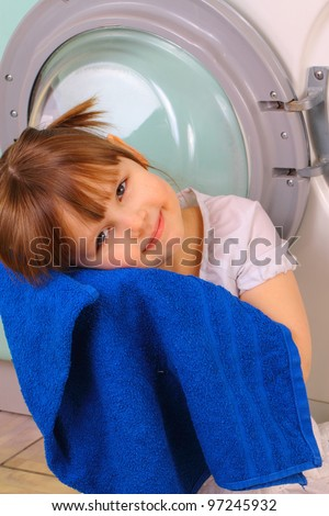 A little girl gets a towel after washing - stock photo