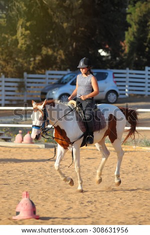 A little girl getting a horseback riding lesson  - stock photo