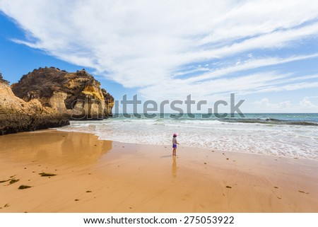 A little girl has fun at Castelejo beach on Algarve, Portugal - stock photo