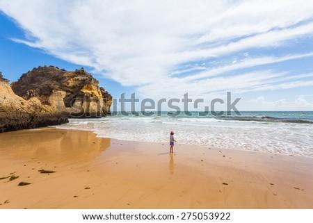 A little girl has fun at Castelejo beach on Algarve, Portugal - stock photo