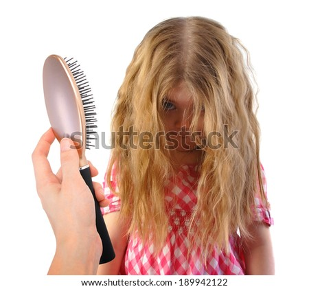 A little girl has tangles and messy hair. A brush is being held up on a white isolated background for a hair dresser or beauty concept. - stock photo