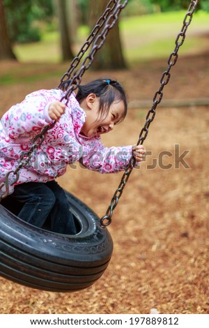 A little girl having a great time on a swing in a playground. - stock photo