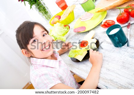 A little girl having breakfast at home. - stock photo