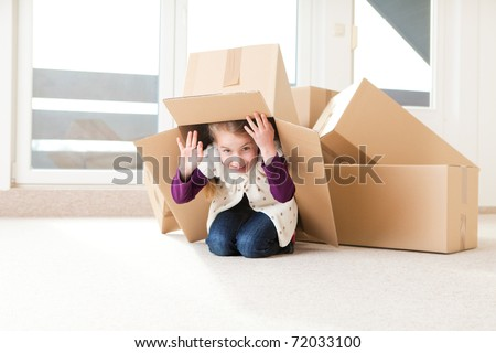 a little girl hiding under a cardboard box, having fun at moving house. - stock photo