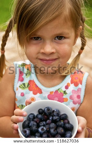 A little girl holding a dish of freshly picked blueberries