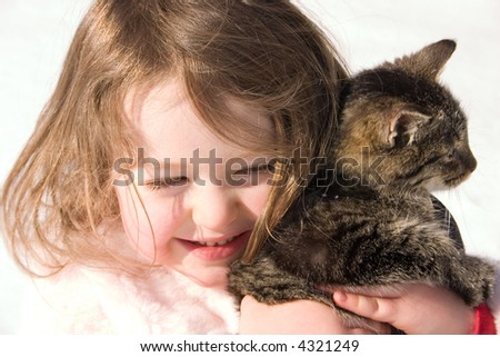a little girl holding her pet kitty - stock photo