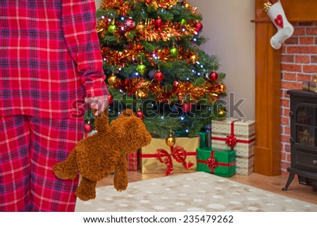 A little girl holding her teddy bear on Christmas morning, gift wrapped presents under the tree and a stocking over the fireplace. Focus is on the bear. - stock photo