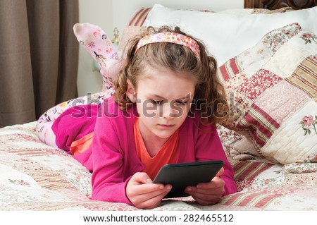 A little girl holds an ebook in her hands and stares intently at the screen.  She is laying on her stomach and propped up on her elbows.