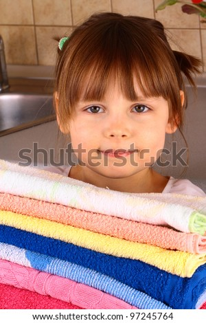 A little girl holds towels after washing - stock photo
