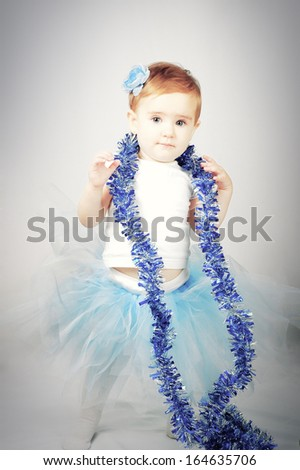 A little girl in a beautiful dress with tinsel - stock photo
