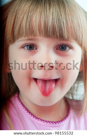 a little girl in a pink shirt posing in studio