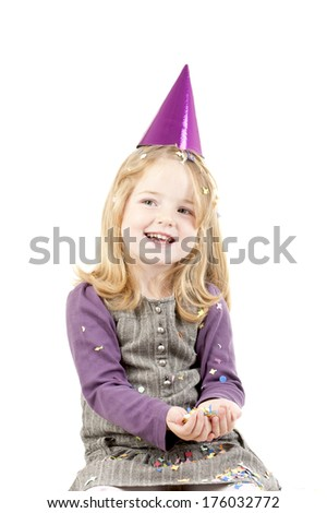 A little girl in a purple party hat smiles as she looks to the right.